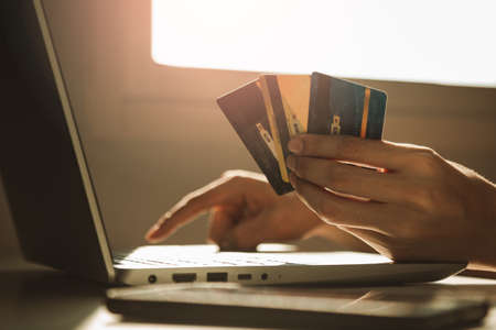 Male hands holding credit cards and using laptop computer at working desk for online shopping while break from work at home, E-commerce, Internet banking. 版權商用圖片