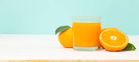 Fresh orange juice in glass and oranges fruit on white wooden table with blue banner background with copy space. 版權商用圖片