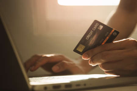 Male hands holding credit card and using laptop computer at working desk for online shopping while break from work at home, E-commerce, Internet banking.