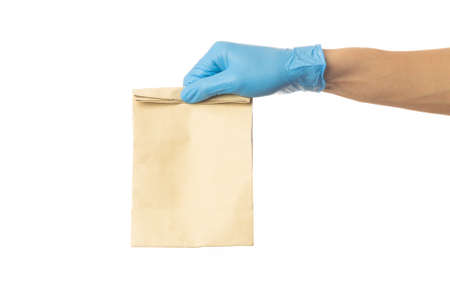 Closeup delivery man hand in medical gloves holding food paper bag isolated on white background, Packaging mockup, Delivery service concept.