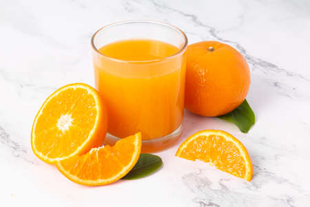Fresh orange juice in glass and oranges fruit on white marble table background.