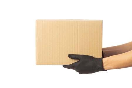 Closeup delivery man hand in medical gloves holding cardboard box isolated on white background, Packaging mockup, Delivery service concept.