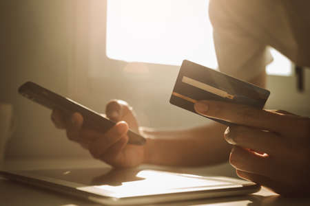 Male hands holding smartphone and credit card at working desk for online shopping while break from work at home, E-commerce, Internet banking. 版權商用圖片