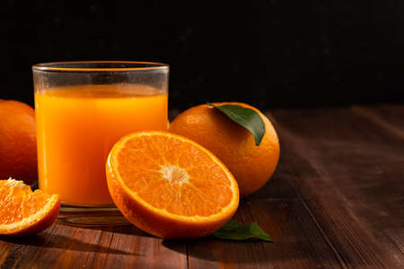 Fresh orange juice in glass and oranges fruit on wooden table background with copy space.
