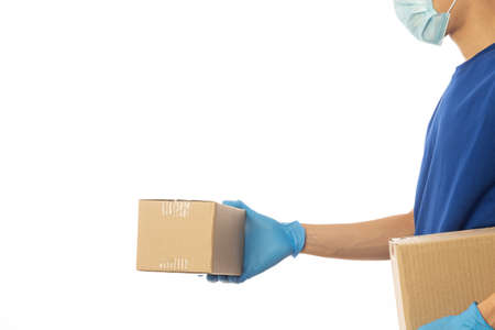 Delivery man hand in medical gloves and wearing mask holding cardboard boxes isolated on white background, Delivery service concept.