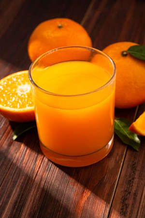 Fresh orange juice in glass and oranges fruit on wooden table background.