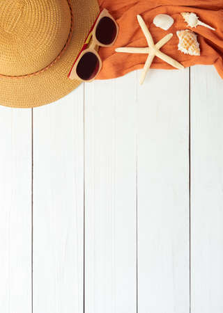Summer background with beach accessories - straw hat, sunglasses, towel on white wood table background top view with copy space.
