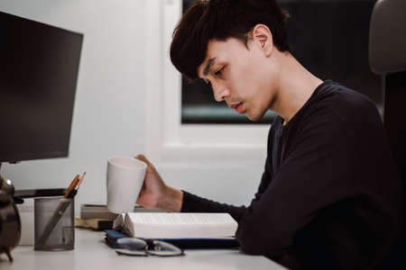 Young handsome asian man reading book and drinking tea at work desk late at night, Knowledge and learning concept.