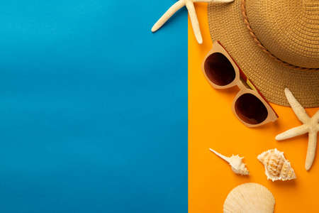 Summer background with beach accessories - straw hat, sunglasses on vibrant orange and blue background top view with copy space. 版權商用圖片