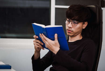Young handsome asian man reading book at work desk late at night, Knowledge and learning concept. 版權商用圖片