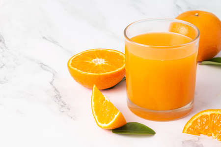 Fresh orange juice in glass and oranges fruit on white marble table background with copy space. 版權商用圖片