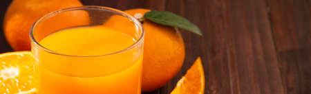 Fresh orange juice in glass and oranges fruit on wooden table banner background with copy space.