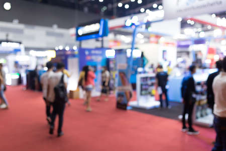 Abstract blur people in exhibition hall event trade show expo background. Business convention show, job fair, or stock market. Organization or company event, commercial trading, or shopping mall marketing advertisement concept. Stock Photo