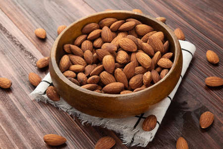 Almonds in wooden bowl on the table, Healthy snack, Vegetarian food. Stock Photo