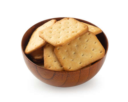 Cracker cookies in wooden bowl isolated on white background with clipping path.