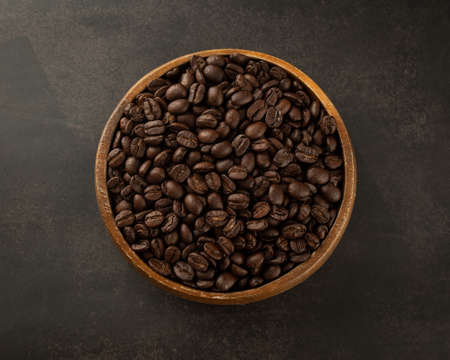 Coffee beans in wooden bowl on grunge background.