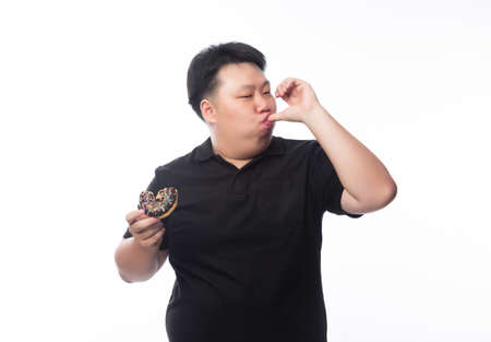 Young Funny Fat Asian man eating chocolate donuts isolated on white background, Unhealthy concept. Фото со стока