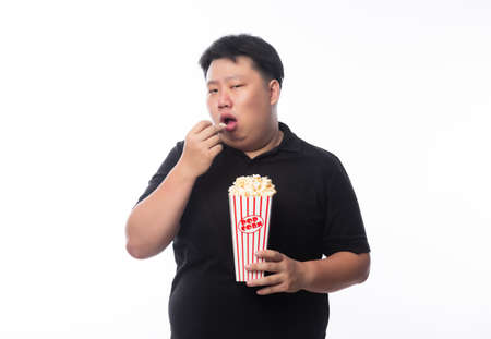 Young Funny Fat Asian man eating popcorn isolated on white background, Unhealthy concept.