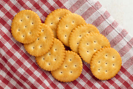 Cracker cookies with tablecloth on white wooden table background. Фото со стока