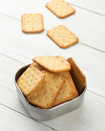 Cracker cookies in a stainless steel bowl on white wooden table background. Фото со стока