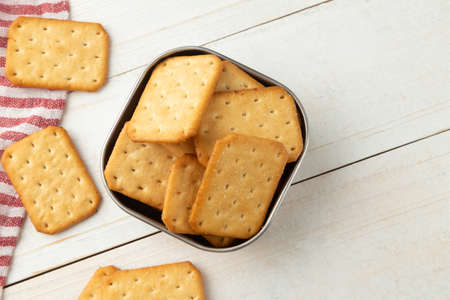 Cracker cookies in a stainless steel bowl with tablecloth on white wooden table background.