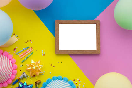 Happy birthday background, Flat lay colorful party decoration with flyer invitation card on pastel yellow, blue and pink geometric background.