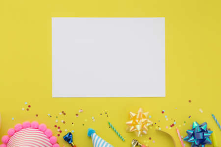 Happy birthday background, Flat lay colorful party decoration with flyer invitation card on pastel yellow background.