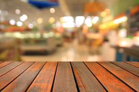 blurred image wood table and abstract generic supermarket people walking shopping