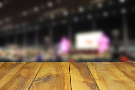 attendee: blurred image wood table and abstract trade show area and people. Blurred image background Stock Photo