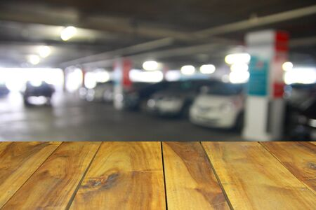 vacant lot: blurred image wood table and abstract of the car parking