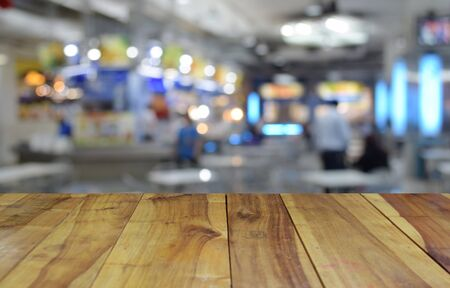 busy restaurant: blurred image wood table and abstract food center with light bokeh