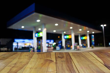 opec: blurred image wood table and abstract gas station at night