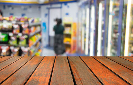 blurred image wood table and abstract minimart convenience store
