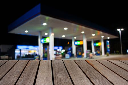 unleaded: blurred image wood table and abstract gas station at night