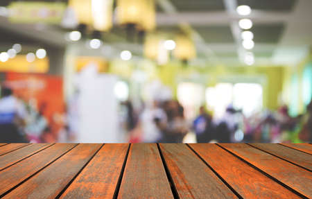 attendee: blurred image wood table and abstract trade show and one stop shopping expo