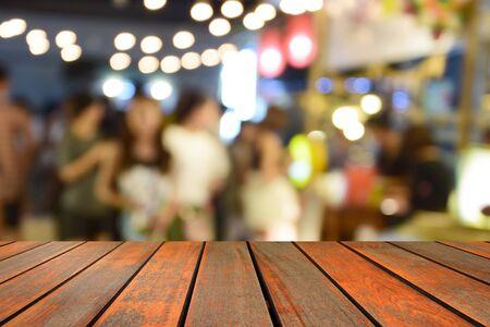 unscharfe Bildholztabelle und -lebensmittel am Nachtfestival mit bokeh Hintergrund