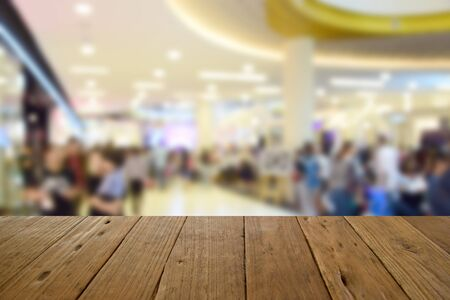 blurred image wood table and people in shopping mall with bokeh
