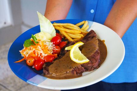 Appetizing stake on plate and golden french fries and green vegetables.