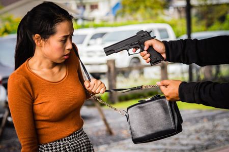 Thief is threatening woman.Robber is robbing woman by gun.Violence and robberry concept. Stock Photo