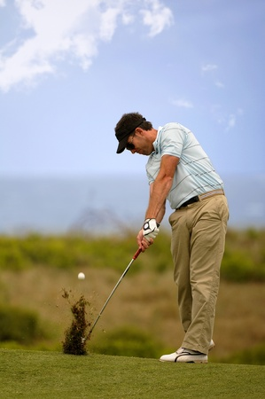 Golfer hitting the ball on the fairway photo