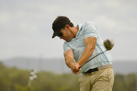 Golfer swings his driver off the tee Stock Photo