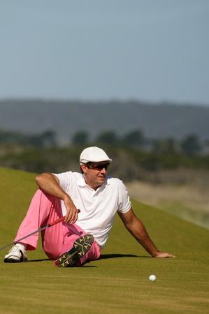 Golfer sites resting on the green Standard-Bild