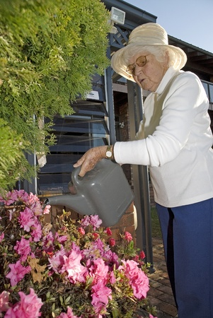 Retired lady, using the watering can to water flowers