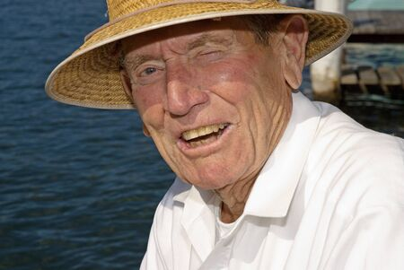 Elderly man with sun hat at waters edge