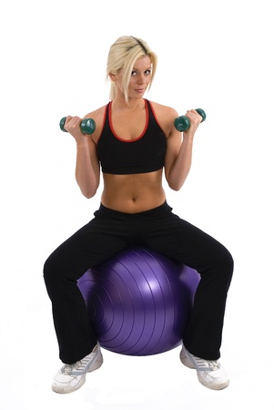 Woman doing weights on a gym ball photo