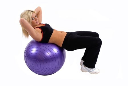 Woman doing sit ups on her gym ball Stock Photo