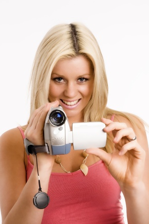 Blond woman films with her camcorder photo