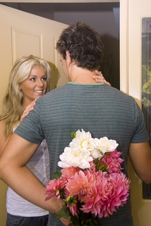 Young attractive woman is greeted at the door with flowers from her boyfriend