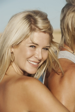 Blond woman smiling at the beach Stock Photo