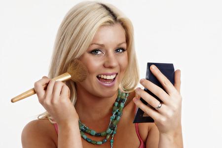Woman applying makeup Standard-Bild